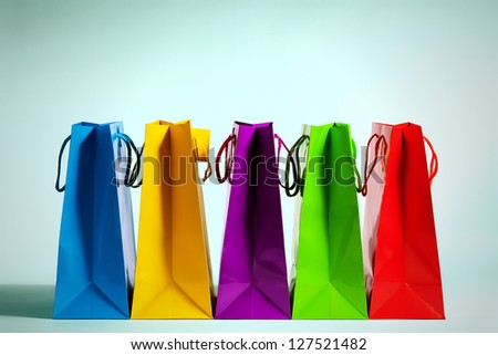 five colorful shopping bags in a row in fashion light - stock photo