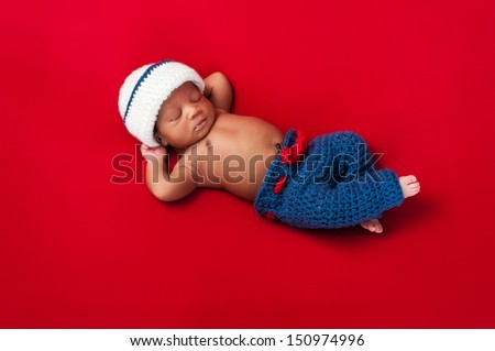 Five day old newborn baby boy wearing a red, white and blue sailor costume and sleeping on his back with his arms behind his head. Shot in the studio on a red background. - stock photo