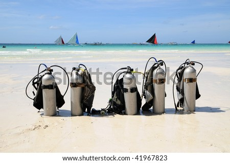 five diving tanks on the white beach with the sailboats in the background - stock photo