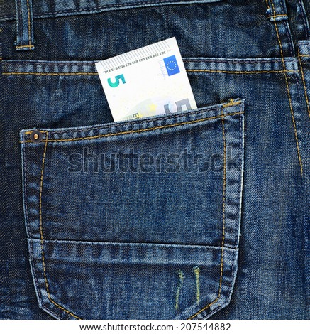 Five euro bank note in a back pocket of a navy blue denim jeans as a background composition - stock photo