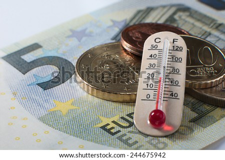 Five euro banknote with some coins and a thermometer showing celsium and fahrenheit temperature - stock photo