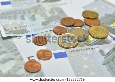 five euro banknotes and euro coins