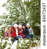 Five female friends sit on snowy pine branches - stock photo
