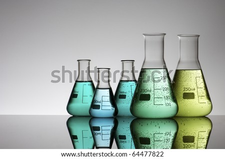 five flasks with colored liquid and a white background - stock photo