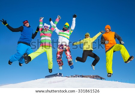 Five friends joyfully jump into the sky over snow drifts in the winter resort