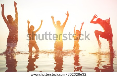 five friends making party at sunrise. boys and girls jumping and dancing in the ocean