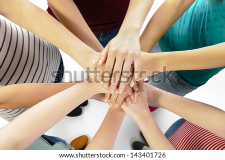 Five girls showing unity with their hands. - stock photo
