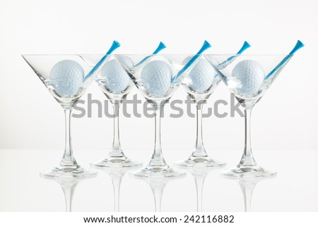 Five glasses of champagne and golf equipments on the glass desk - stock photo