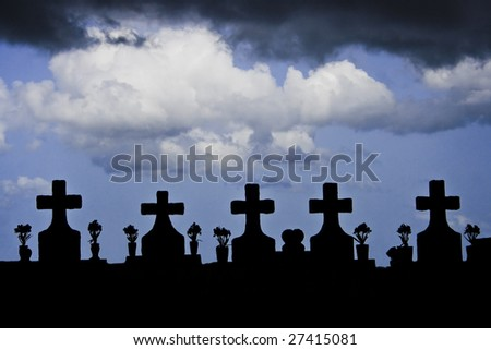 Five grave markers under puffy white and storm clouds - stock photo