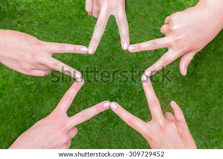 Five hands of teens making star shape together above grass - stock photo