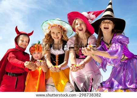 Five Happy Children Holding Candies in Halloween Costumes of Witches, Pumpkin and Devil at the Blue Sky - stock photo