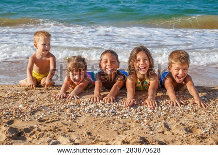 Five happy kids stretched out his arms on the beach