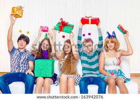 Five high school students hold present boxes in hands - stock photo