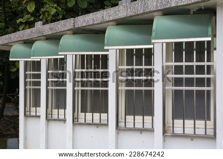 Five Iron Barred WIndows With Green Rain Shelters Arranged in A Row, From Near to Far. - stock photo