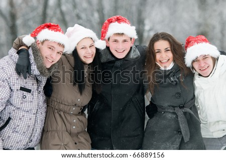 five jolly young boys and girls embracing each other on shoulders wearing red hat at snowy winter outdoors