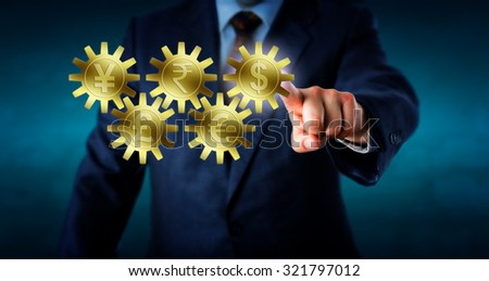 Five major currencies interlocking like a gear train. Golden cogs embossed with Dollar, Euro, Rupee, Pound Sterling and Yen or Yuan symbol. Hand of a trader is touching and highlighting the Dollar. - stock photo