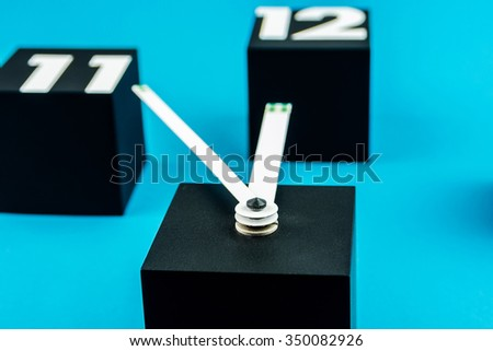 five minutes before twelve with black cubes as digits of big clock on blue background - stock photo