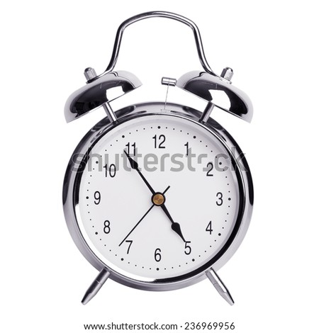 Five minutes to five on a round alarm clock - stock photo