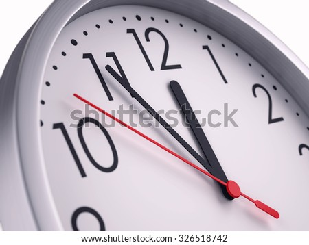 Five minutes to twelve - Closeup of hands on wall clock face - stock photo