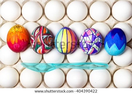 five multicolored painted easter eggs lying on white tray, different patterns, blue knife, holiday celebration food photography