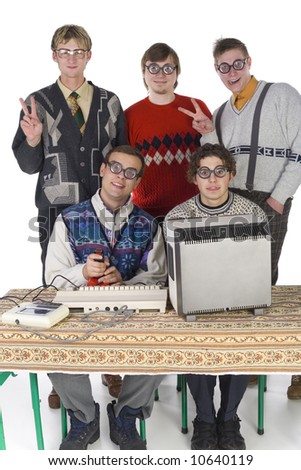 Five nerdy guys looking at camera and smiling. Two of them are sitting in front of old-fashioned computer. Others are standing behind them. They are looking very funny. Front view, white background - stock photo