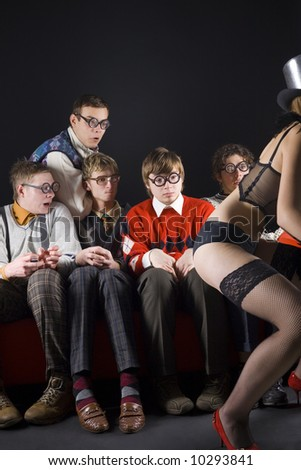 Five nerdy guys sitting in front of dancing stripteaser. They are looking scared. Front view, whole body - stock photo