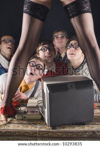 Five nerdy guys sitting in front of old-fashioned computer and stripteaser. They are looking fascinated. Front view - stock photo
