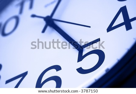 Five o clock - detail of wall office clock showing it's time to go home. Selective focus on number 5, blue tint - stock photo