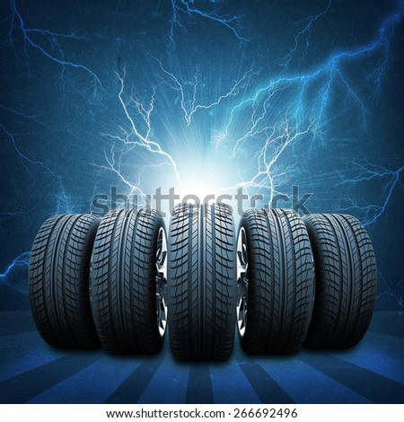 Five of new car wheels. Abstract background is concrete wall, lightning and stripes at bottom - stock photo