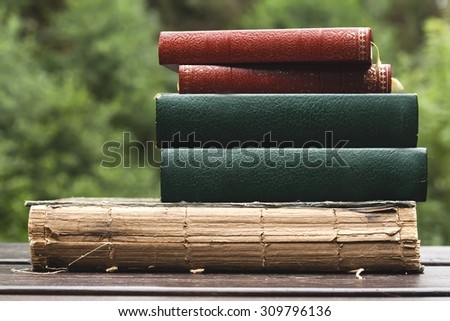 five old books on a garden table  - stock photo