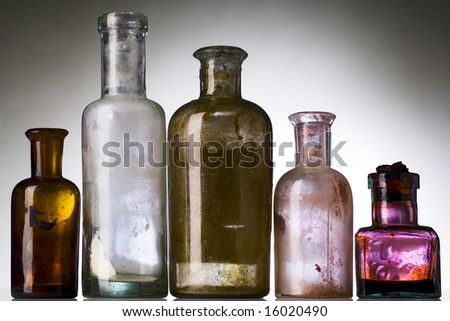 five old, dirty, pharmacist's bottles