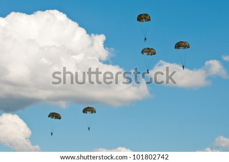 five parachutists on blue sky with white clouds - stock photo