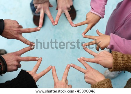 Five people form a star with their fingers - stock photo