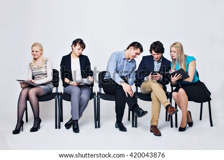 five people in business suits sitting on chairs on a white background