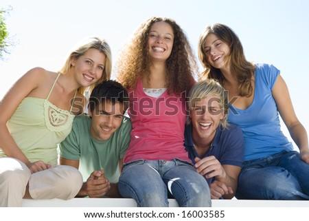 Five people on balcony smiling - stock photo
