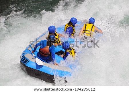 Five people wearing safety gear ride through river rapids. - stock photo