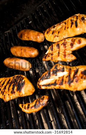Five pieces of chicken and sausages cooking on the barbeque