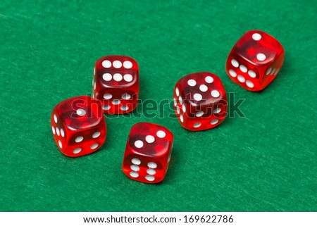 five playing red dices on green casino table - stock photo