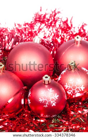 five red Christmas baubles and tinsel isolated on white background