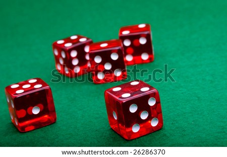 five red dice on green backgound