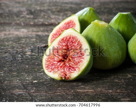Five ripe figs on a wooden table with one fig cut in half
