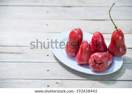 Five Rose apples on wooden table