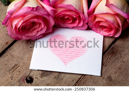 Five roses and white card with a red heart on wooden background. - stock photo