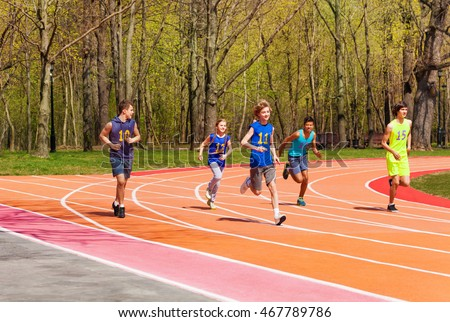Five running teenage athletes in the stadium