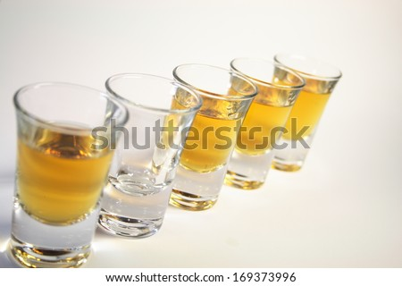 five schnapps glasses with liquid