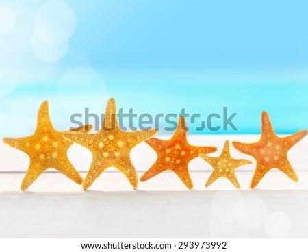 Five sea stars on the summer beach - stock photo
