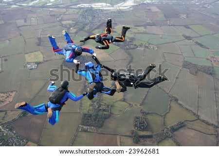 Five skydivers performing formations - stock photo