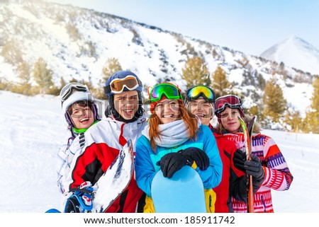 Five smiling friends with snowboards - stock photo