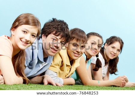 Five smiling teenagers lying on grass in a row, looking at camera and smiling