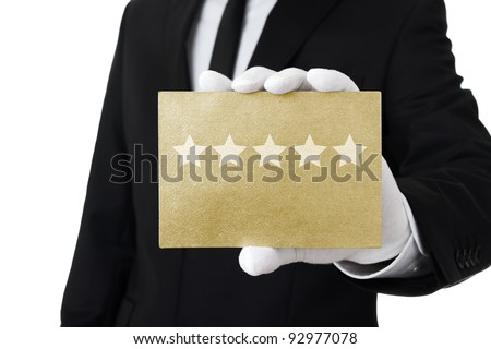 Five stars service, well dressed man holding gold card with 5 stars on it - stock photo